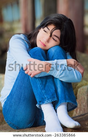 Sad biracial teen girl in blue shirt and jeans sitting on rocks along lake shore with knees pulled up to chest, lonely expression - stock photo