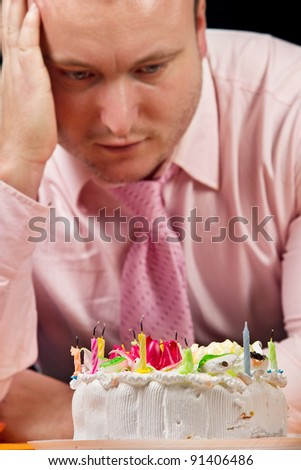 Sad birthday man with cake and candle - stock photo