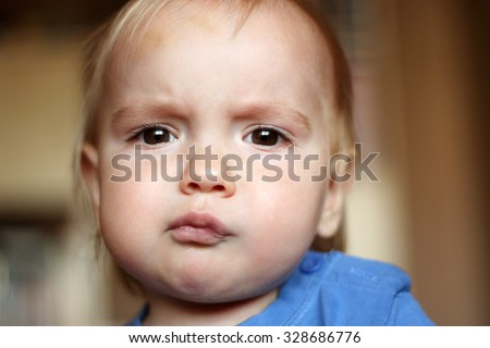 Sad blond baby boy with serious fun grimace and tightened mouth, indoor portrait - stock photo
