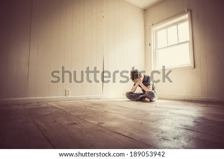 Sad boy alone in a bare room - stock photo