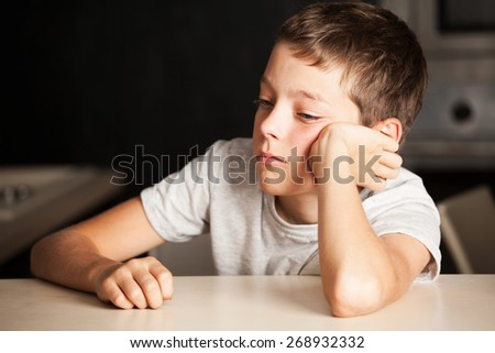 Sad boy at home. Unhappy child. Emotions stress at teenager - stock photo