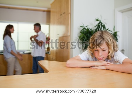 Sad boy has to listen to his fighting parents - stock photo