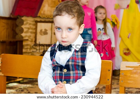 Sad boy in a vest and bow tie seated on a chair at the party in the kindergarten - stock photo