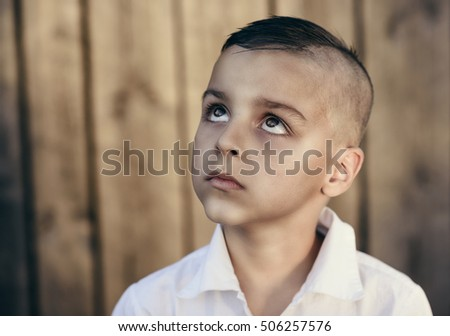 sad boy looking up,Old wooden background in behind