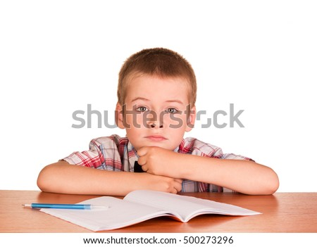 Sad boy sitting at a table on a notebook, a pen isolated on white background.