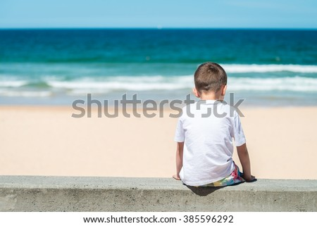 Sad boy sitting at he beach and thinking about something - stock photo