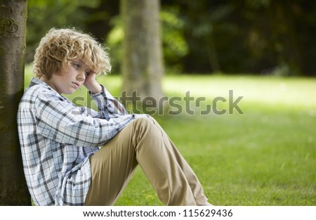 Sad Boy Sitting In Park - stock photo