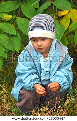 sad boy sitting in the grass outdoor - stock photo