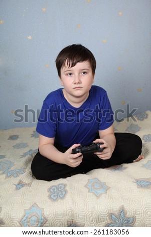 Sad boy sitting on the sofa with a joystick - stock photo