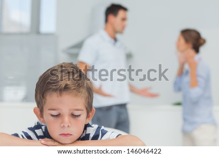 Sad boy while parents quarreling in the kitchen - stock photo