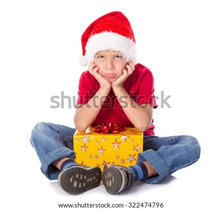 Sad boy with gift box in christmas hat, sitting on the floor, isolated on white - stock photo