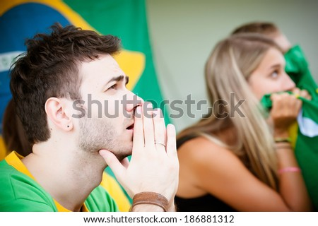 sad brazilian supporters at stadium - Stock Image - stock photo