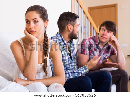 Sad brunette girl and two men at home: problems of love triangle. Selective focus