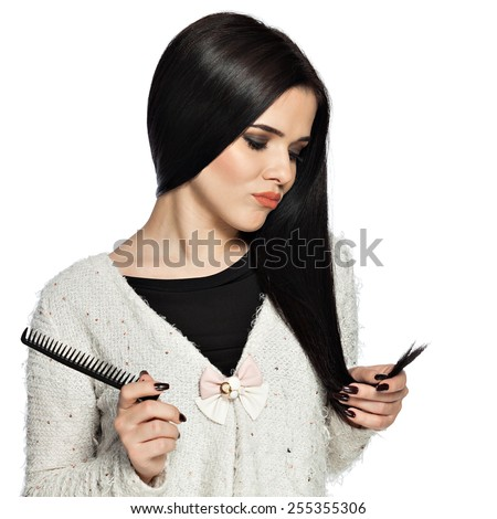 Sad brunette young woman holding her hair, and a comb.  Gorgeous white caucasian female model feeling disappointed about the split ends. - stock photo
