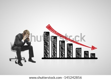 sad businessman sitting on chair with falling 3d chart - stock photo