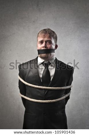 Sad businessman tied and muffled - stock photo