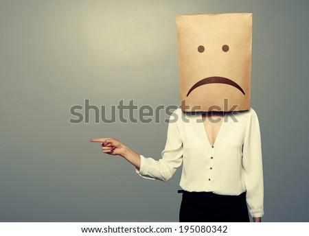 sad businesswoman pointing at something over dark background - stock photo