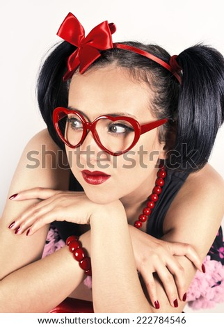 Sad charming girl in glasses with red case - stock photo