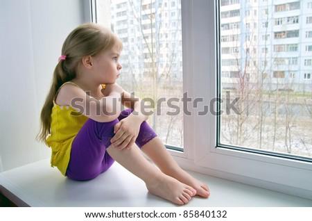 Sad child at the window. - stock photo