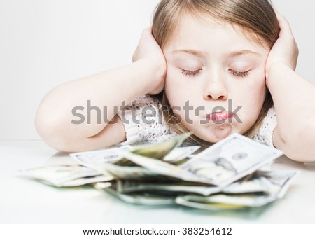 Sad child girl cover her ears and close eyes with money on table stress concept