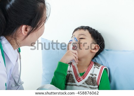 Sad child having respiratory illness helped by health professional with inhaler. Pediatrician take care asian boy with asthma problems making inhalation with mask on his face at hospital. - stock photo
