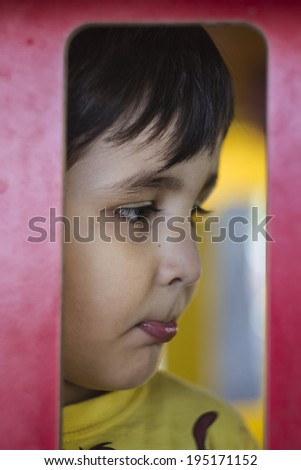 Sad child in a park putting expressive faces - stock photo