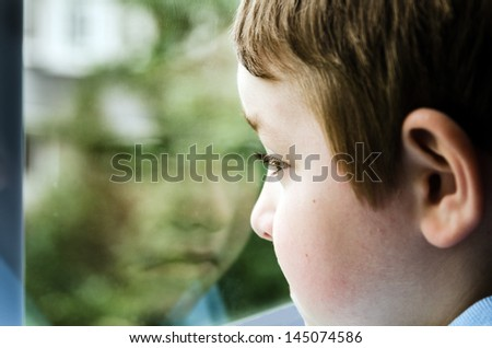 Sad child looking out window with reflection on gloomy day - stock photo