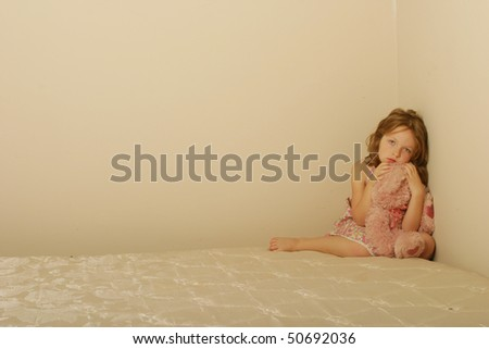 Sad child sitting alone on old mattress with a teddy bear - stock photo