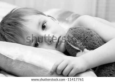Sad child with a teddy bear - stock photo
