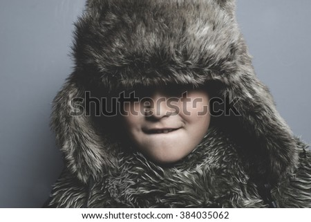 Sad child with fur hat and winter coat, cold concept and storm