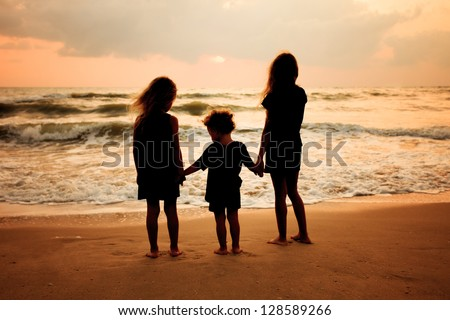 sad children on the beach - stock photo