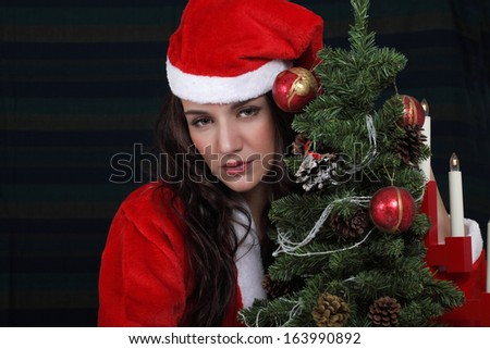 Sad Christmas girl in Santa dress with lonely expression