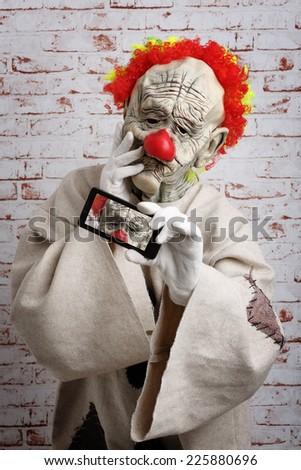 Sad clown makes selfie on cellphone - stock photo