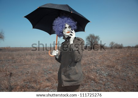 Sad clown outdoors hodling black umbrella - stock photo