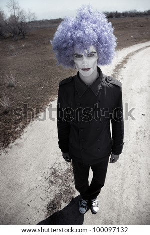 Sad clown outdoors standing on a country road - stock photo