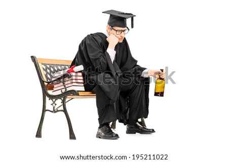 Sad college graduate drinking alcohol seated on bench isolated on white background - stock photo