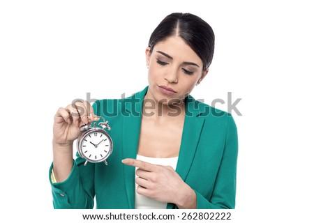 Sad corporate woman pointing alarm clock - stock photo