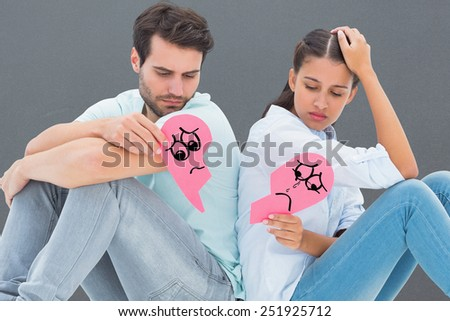 Sad couple sitting holding two halves of broken heart against grey - stock photo