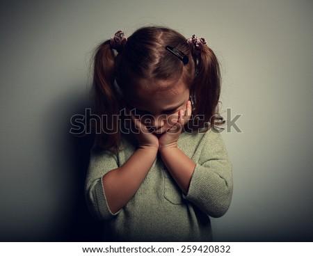 Sad crying alone kid girl on dark background. Closeup portrait - stock photo