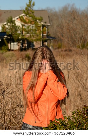 Sad crying girl, covering her face. - stock photo