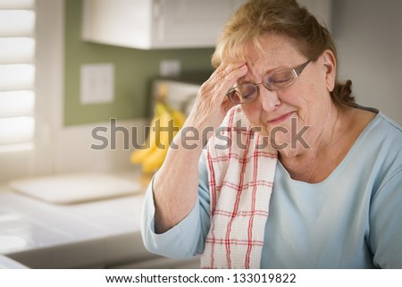 Sad Crying Senior Adult Woman At Kitchen Sink in Home. - stock photo