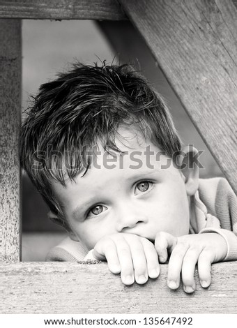 sad depressed little boy peering from beyond his hands - stock photo