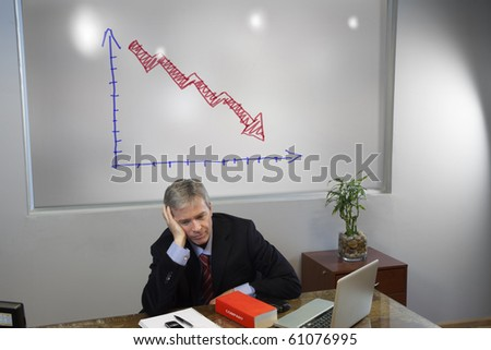 Sad depressed manager in his office with a chart showing loss - stock photo