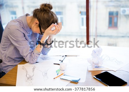Sad despaired young woman fashion designer sitting in office with sketches on table - stock photo