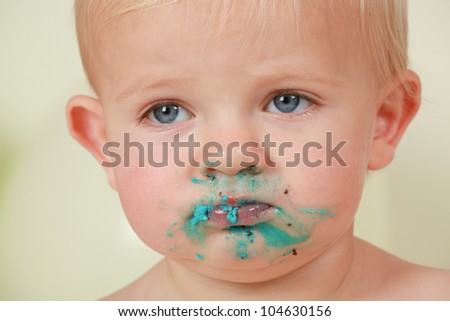 sad dirty blond hair,blue eyed boy staring to the right.with blue icing and chocolate birthday cake messed all over his face.Pouting as if he wants more cake. - stock photo