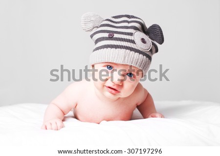 Sad, dissatisfied little baby boy lying on bed and looking into camera.  - stock photo