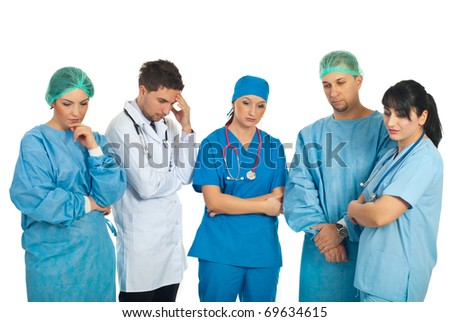 Sad doctors team with problems standing in a row and thinking at solutions isolated on white background - stock photo