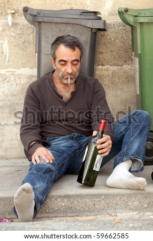 sad drunk man sitting on sidewalk near trashcan