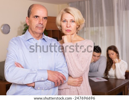 Sad elderly couple on a background of adult children with documents - stock photo