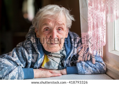 Sad elderly woman portrait at the table. - stock photo